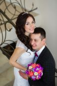 Just married do embrace on the stairs — Стоковое фото