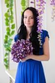 Portrait of a girl in a blue dress with flowers — Stock fotografie