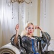 Lady in medieval dress sits on a sofa under the chandelier — Stock Photo #71805161