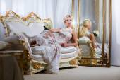 Woman in a magnificent dress lying on the sofa and mirrors — Stock Photo