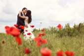 Bride and groom posing in poppy fields — Stock Photo