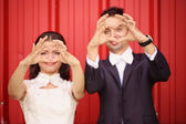 Bride and groom making heart sign with their hands — Stock Photo