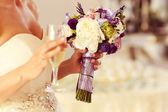 Bride holding wedding bouquet and champagne glass — Stock Photo