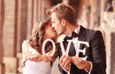 Happy bride and groom holding LOVE letters — Stock Photo