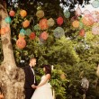 Bride and groom kissing under colorful lamps — Stock Photo #74193333
