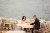 Bride and groom sitting at table next to the sea — Stock Photo