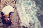 Happy bridal couple laying on stones next to the sea — Stock Photo