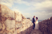 Bride and groom in stone pathway — Stock Photo