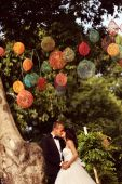 Bride and groom kissing under colorful lamps — Stock Photo