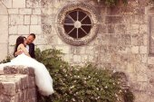 Bride and groom posing near old house — Stock Photo