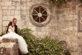 Bride and groom embracing near stone wall — Stockfoto