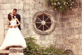 Bride and groom embracing near stone wall — 图库照片