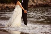 Bride and groom holding hands at the beach — 图库照片