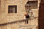 Bride and groom kissing on stairs in old city — Stock Photo