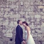 Bride and groom kissing near brick wall — Stock Photo #74204967