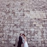 Bride and groom kissing near brick wall — Stock Photo #74204969