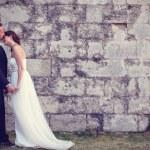 Bride and groom kissing near brick wall — Stock Photo #74205929