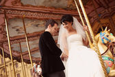 Happy bride and groom on carousel — Stock Photo