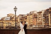 Bride and groom in the city laughing and hugging — Stock Photo