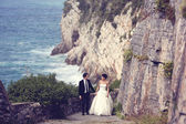 Bride and groom holding hands near seaside — Stock Photo