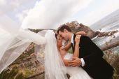 Happy bridal couple kissing near seaside — Stock Photo