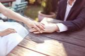 Holding hands with wedding ring in the sunlight — Stock Photo