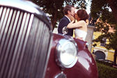 Bride and groom having fun near retro car — 图库照片