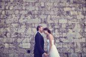 Bride and groom kissing near brick wall — Stock Photo