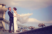 Bride and groom having fun on a bridge — Stock Photo