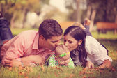 Parents with baby girl sitting on grass in the park — Stock Photo
