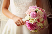 Bride holding a beautiful peonies bouquet — Stock Photo