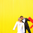 Bride and groom posing against a yellow wall, holding L and M letters — Stock Photo #74225419