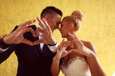 Bruide and groom making love sign with their hands — Stock Photo