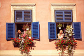 Bride and groom having fun from window of old house — Stock Photo