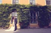Bride and groom embracing in front of a beautiful house covered with ivy — Stock Photo