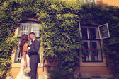 Bride and groom embracing in front of a beautiful house covered with ivy — Stok fotoğraf