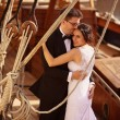 Bride and groom embracing near big ship with strings — Stock Photo #74289775