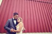 Cheerful bride and groom against red wall — Stock Photo