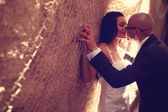 Bride and groom against a wall with trammel — Stock Photo
