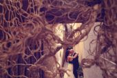 Bride and groom photographed through ropes — Stock Photo