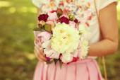 Hands of a woman holding beautiful peonies bouquet — Stock Photo