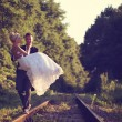 Groom carrying his bride on a railroad — Stock Photo #74384369