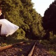 Groom carrying his bride on a railroad — Stock Photo #74384371