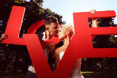 Bride and groom holding big love letters — Stock Photo