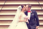 Bruid en bruidegom kussen naast ontdaan muur — Stockfoto