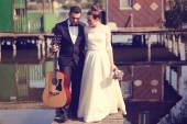 Bride and groom on a wooden bridge near lake — Stock Photo