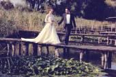 Bride and groom on wooden bridge — Stock Photo