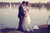 Bride and groom near lake — Stock Photo