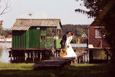 Bride and groom on wooden bridge near lake — Stock Photo