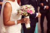 Hands of a bride holding her wedding bouquet — Stock Photo